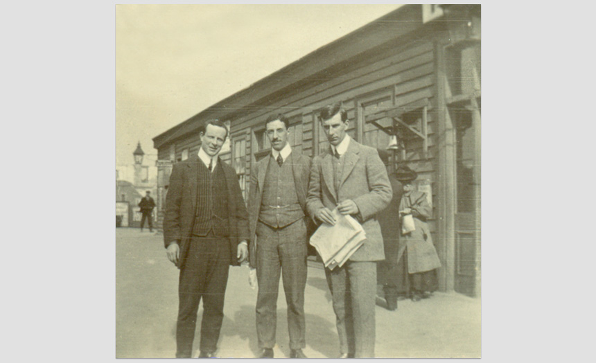 Edward Theomin with 2 other young men outside a (Dunedin) Railway station. One of a set of ten snapshots of a picnic outing, (early 1900's).