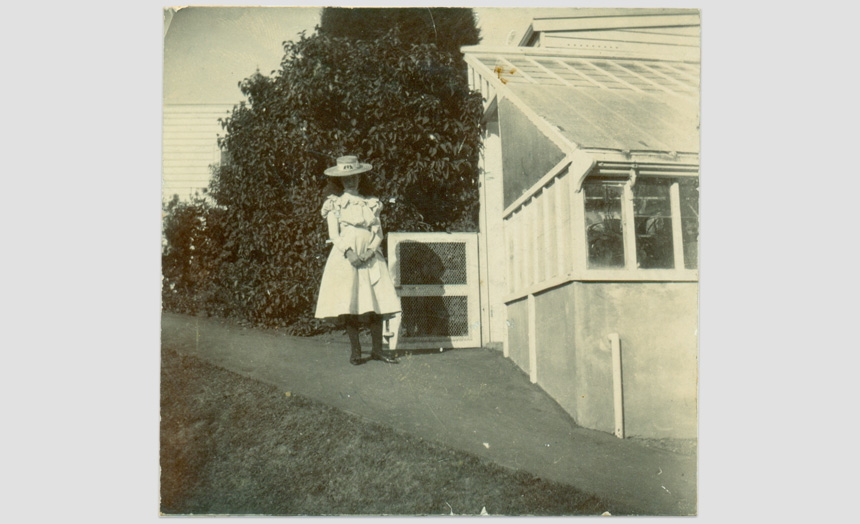 Dorothy Theomin. As a child, taken outside the greenhouse at the first Olveston. Inscribed on back 'Please do not call me till 8 o'clock'.